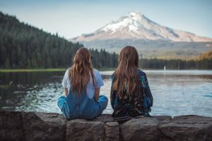Mtaf interview - two young women sit facing the mountains