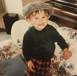 A young rory smiles at the camera in a flat cap
