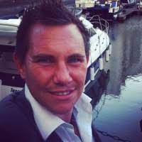 David takes a selfie at a harbour. A boat is behind him and he wears a smart shirt with a stiff white collar and a blue jacket